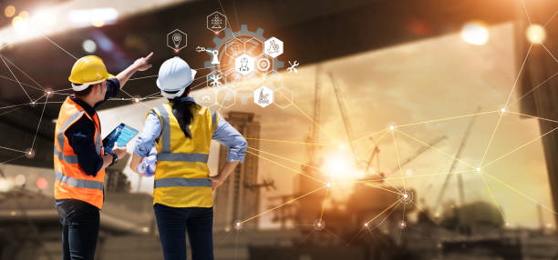Engineer and Architect analyzing of under construction project with technology and new innovative on digital tablet and icon network of construction on virtual interface. stock photo
