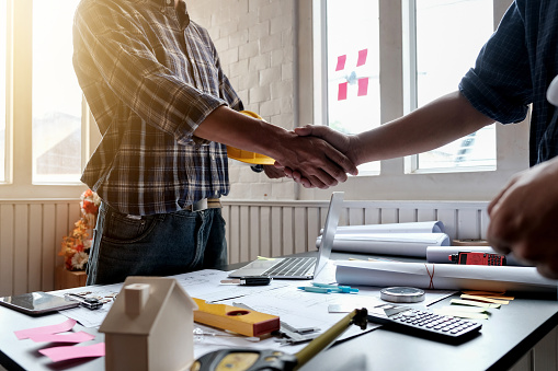 912867216 istock photo Engineer and architect handshake at meeting with successful construction project. 1174841505