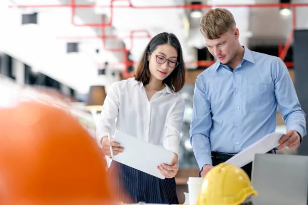 Equipo de ingenieros y arquitectos que planean y discuten sobre construcción de edificios en el escritorio de oficina. - foto de stock