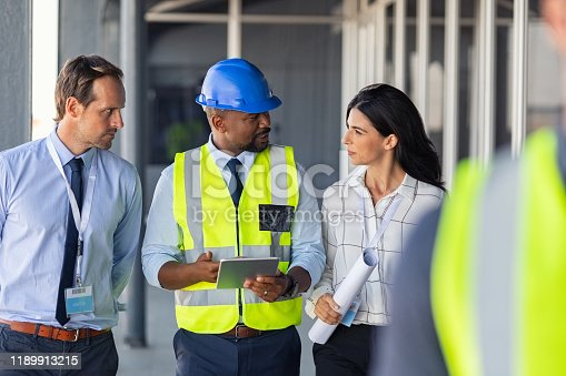 Team of construction workers discussing project details with executive supervisor holding blueprints and digital tablet. Team of architects and civil engineers inspecting construction site. Structural african engineer and architect with work vests discuss the construction process.