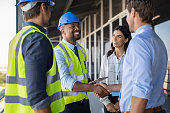 Smiling engineer shaking hands at construction site with happy architect. Handshake between cheerful african construction manager with businessman at bulding site. Team of workers with architects and contractor conclude an agreement with safety uniform.