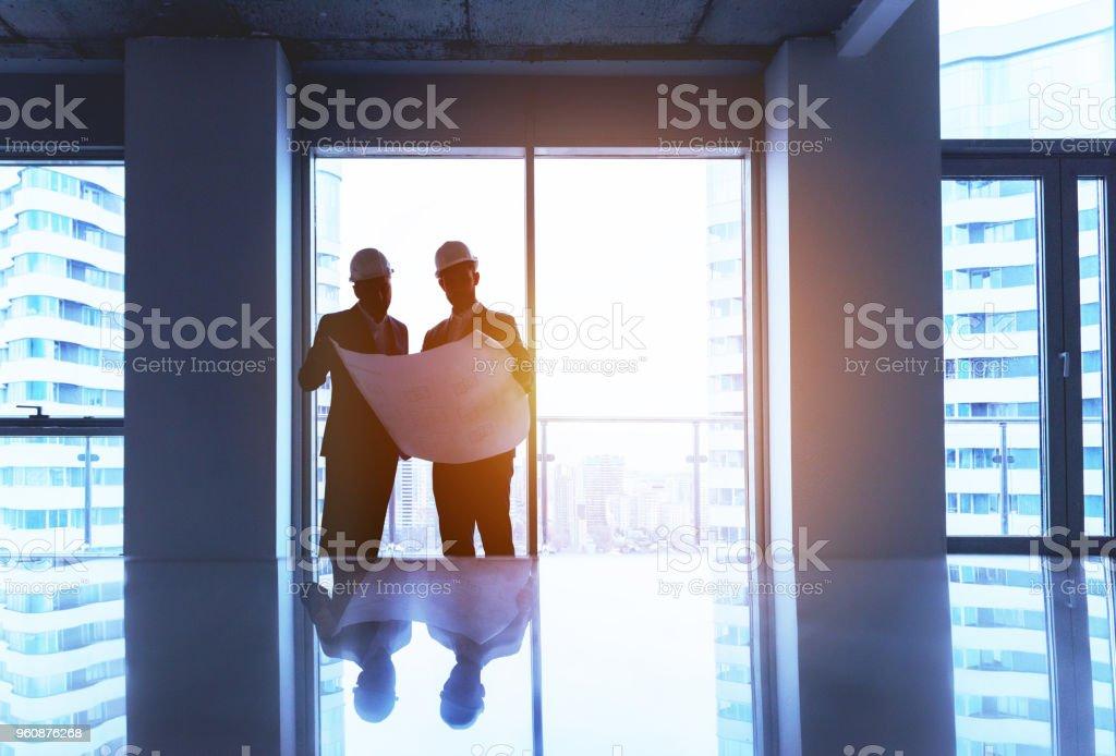 Ingeniero y hombre de negocios con plan en la oficina vacía - foto de stock