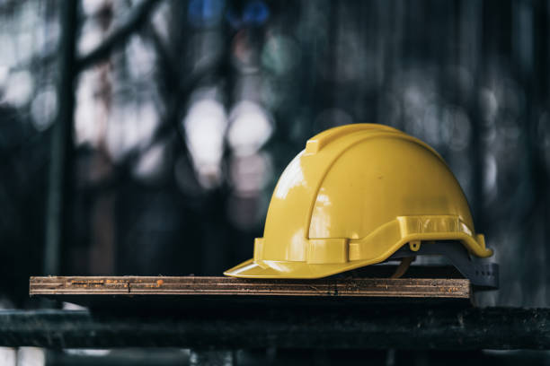 engineer and construction ideas concept with yellow helmet equipment tools at construction site engineer and construction ideas concept with yellow helmet equipment tools at construction site hardhat stock pictures, royalty-free photos & images