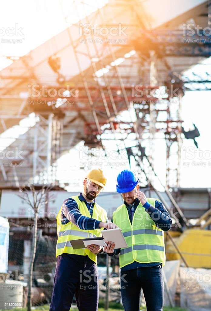 Engineer and construction site manager dealing with blueprints and plans stock photo