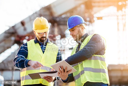 istock Engineer and construction site manager dealing with blueprints and budget 518527996