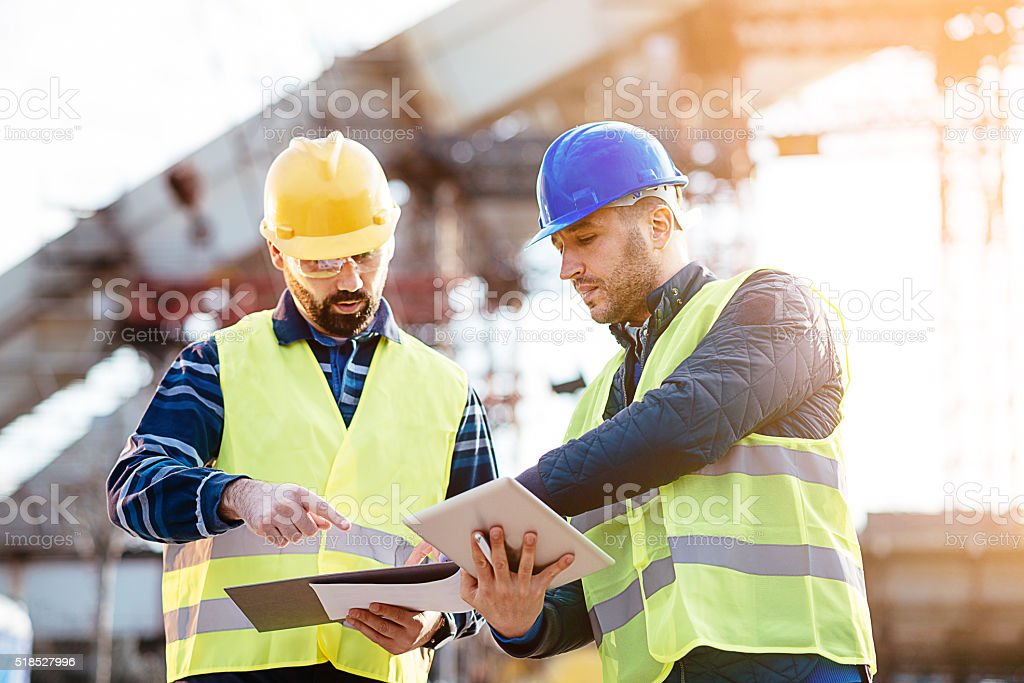 Engineer and construction site manager dealing with blueprints and budget stock photo