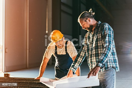 istock Engineer and construction worker checking checking blue print 609721708