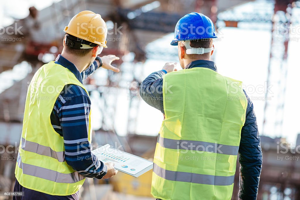 Engineer and contractor having brief meeting on construction site stock photo