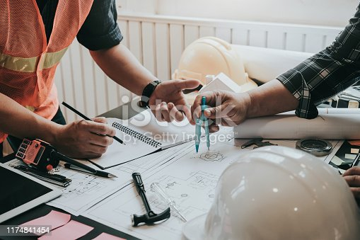1174841541 istock photo Engineer and contractor planning projects together at desk with blueprints. 1174841454