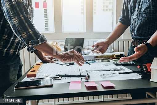 1174841541 istock photo Engineer and contractor planning projects together at desk with blueprints. 1174841461