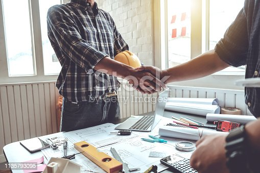 istock Engineer and contractor shaking hands success of the project work together. 1135793095