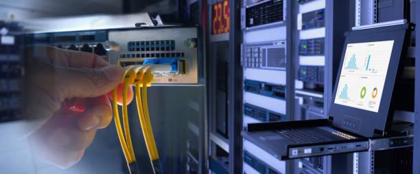 ingenieur und lwl-kabel auf netzwerk-router-switch und monitor graph anzeigen im hintergrund im technologie zentrum datenraum. widescreen - glasfaser telekommunikationsgerät stock-fotos und bilder