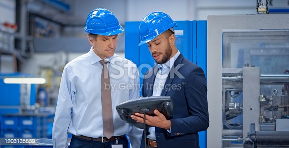 Engineer and supervisor discussing while operating industrial remote control in factory.