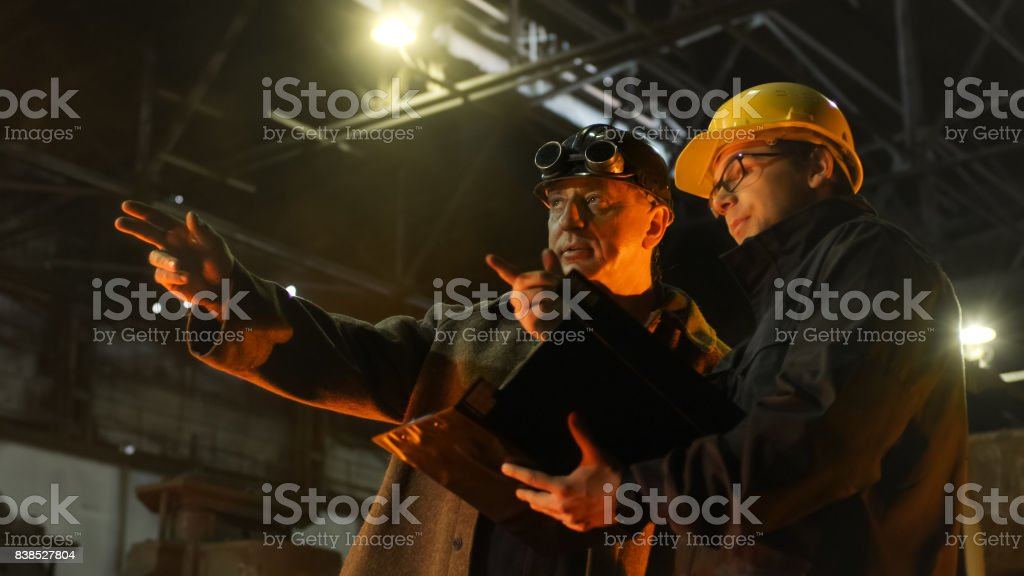 Engineer and Worker Have Conversation in Foundry. Engineer Using...