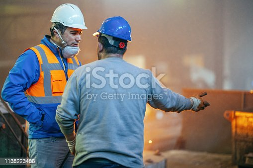 Engineer and Worker Have Conversation in Foundry.