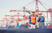 istock Engineer and Worker man in hardhat and safety vest checking control loading containers box from cargo, Teamwork concept 1214448051