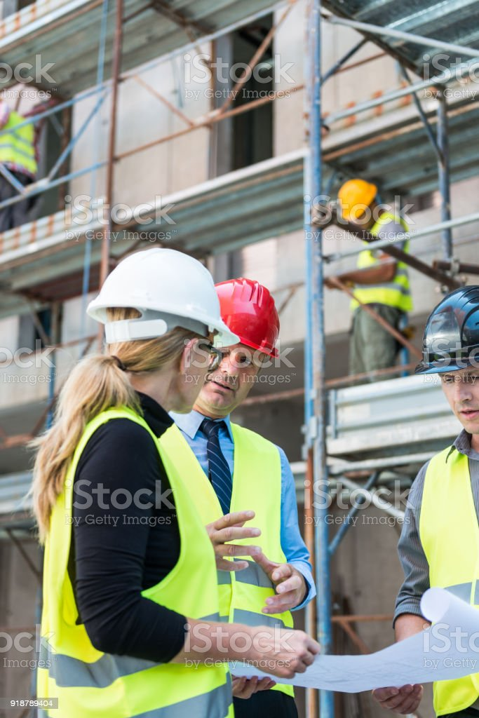 Engineer, Architect And Foreman Talking At Construction Site stock photo