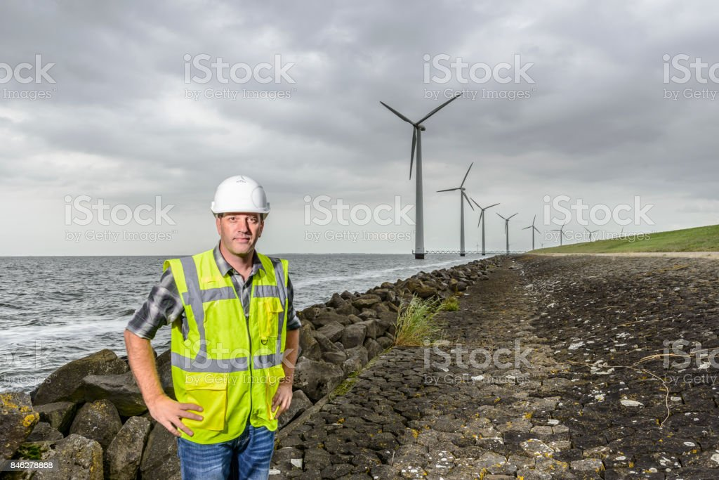 Engineer at an offshore wind turbine park during an overcast day stock photo