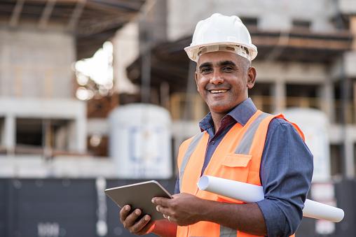 Engineer at construction site, using digital tablet