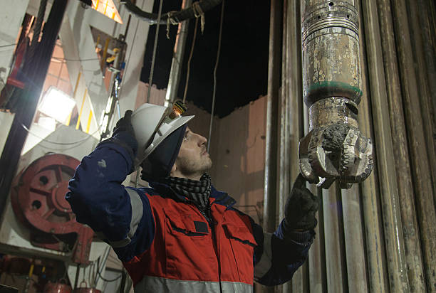 Engineer at rig site with drill bit looking upstairs Drilling Engineer in protective workwear is looking at drill string while pooling out BHA (bottom hole assembly) and holding drill bit drill bit stock pictures, royalty-free photos & images