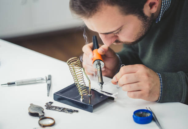 Engineer At Work Young Caucasian engineer At Work. soldering iron stock pictures, royalty-free photos & images