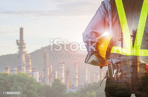 Double exposure of engineer behind with overload tool holding yellow helmet for safety of the workers, Blurred Oil refinery background.