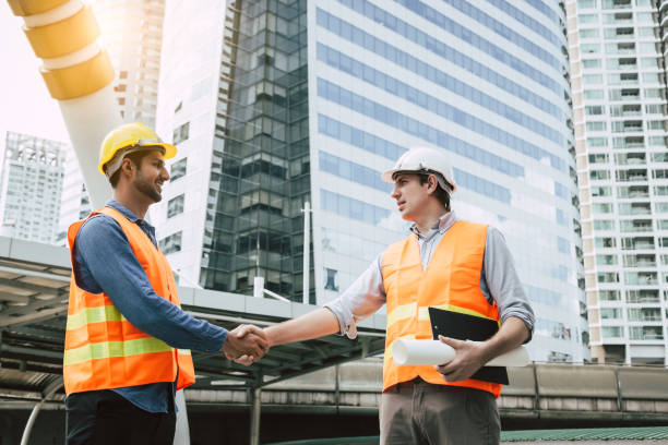 Engineer Boss get handshake, saying thank you to blue collar worker or team for doing work successfully. Employee happy. Blue collar workers men wear hard hat for safety. Engineer man hold blue print stock photo