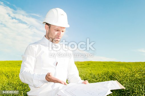 623909418 istock photo Engineer builder is dissatisfied with poor project documentation. Worker with blueprints on background of meadow and blue sky with white clouds during day. geodesist chooses site for construction. 943085002