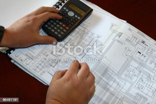 Electronic engineer or student calculating values from a circuit diagram .