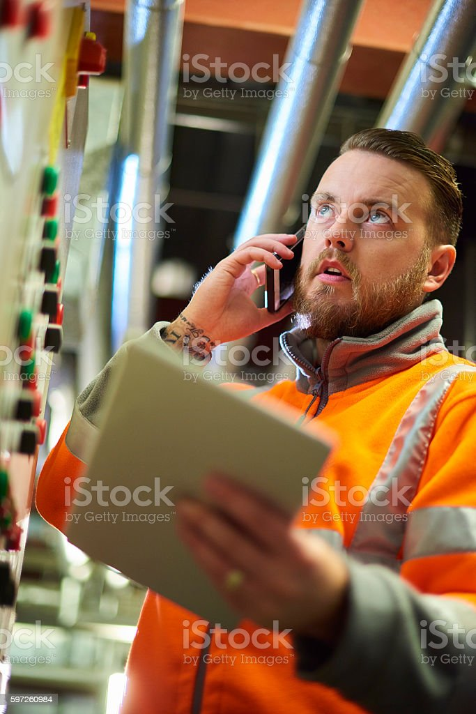 Engineer calling tecnical support stock photo