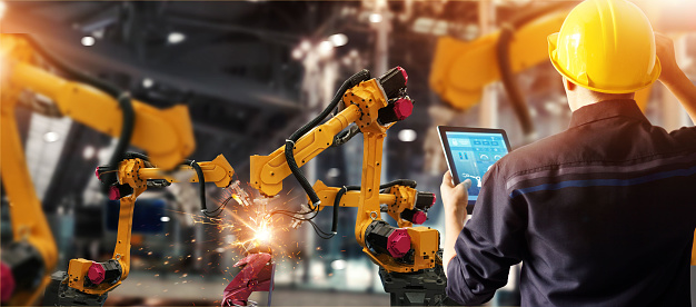 istock Engineer check and control welding robotics automatic arms machine in intelligent factory automotive industrial with monitoring system software. Digital manufacturing operation. Industry 4.0 1025742788