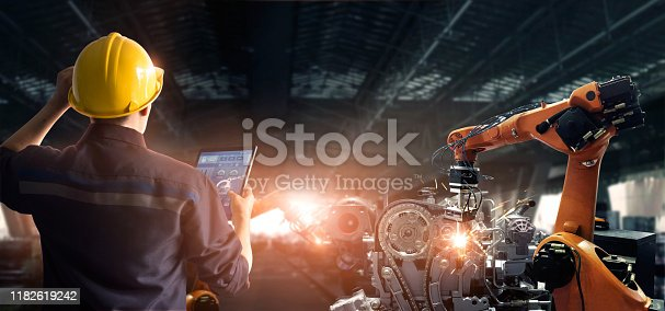 1091790362 istock photo Engineer check and control welding robotics automatic arms machine in intelligent factory automotive industrial with monitoring system software. Digital manufacturing operation. Industry 4.0 1182619242