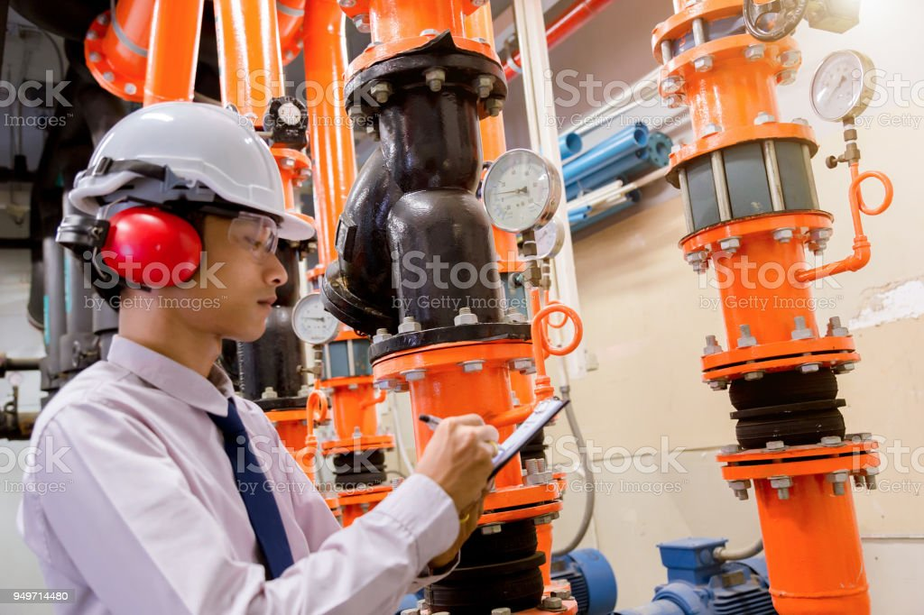 Engineer checking Condenser Water pump and pressure gauge , chiller water pump with pressure gauge.System ready. stock photo