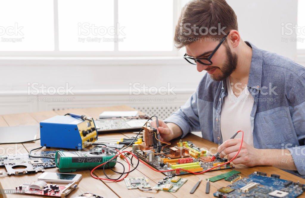Ingenieur-Motherboard mit Multimeter prüfen – Foto