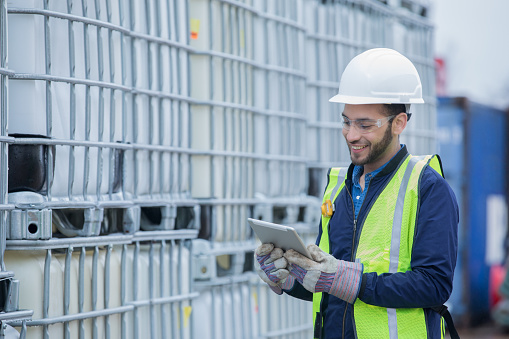 Young adult Hispanic man is chemical engineer checking inventory shipment of chemical crates on oil and gas pipeline job site. Man is wearing safety gear and using a digital tablet.