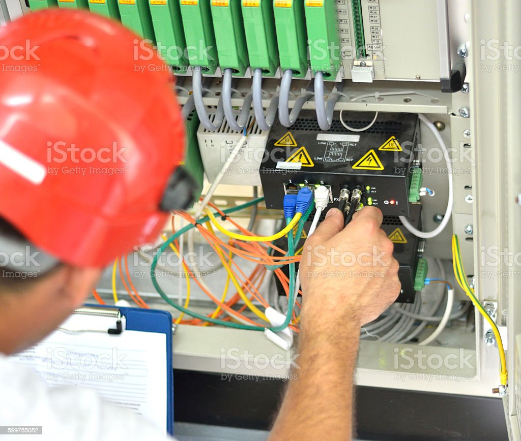 Engineer Connecting Fiber Optic Cable to the Switch stock photo