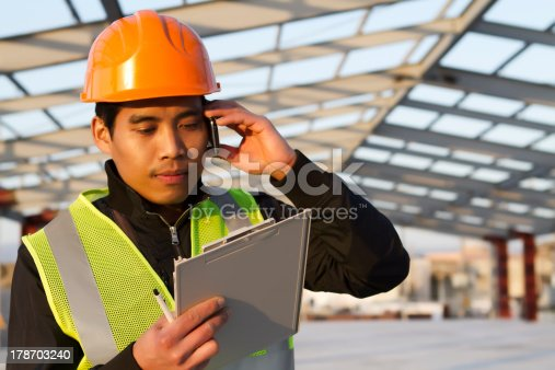 istock Engineer construction talking mobile phone under new building 178703240