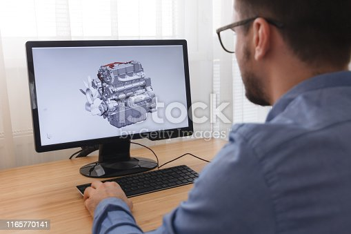 istock Engineer, Constructor, Designer in Glasses Working on a Personal Computer. He is Creating, Designing a New 3D Model of Car Engine, Motor in CAD Program. Freelance Work 1165770141