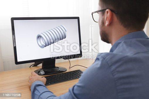 istock Engineer, Constructor, Designer in Glasses Working on a Personal Computer. He is Creating, Designing a New 3D Model of Mechanical Component in CAD Program. Freelance Work 1165770208