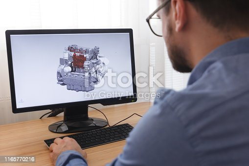 istock Engineer, Constructor, Designer in Glasses Working on a Personal Computer. He is Creating, Designing a New 3D Model of Car Engine, Motor in CAD Program. Freelance Work 1165770216
