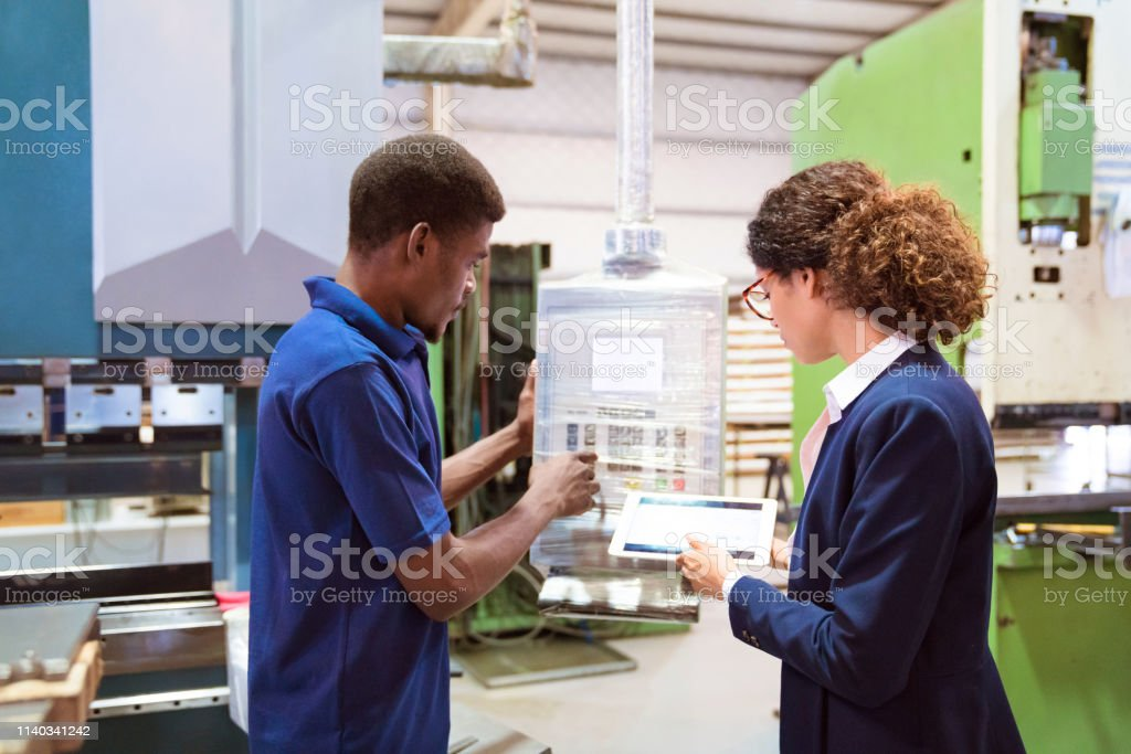 Engineer controlling machine in factory by manager Side view of engineer controlling machine in factory. Female manager is on visit in manufacturing company. She is holding digital tablet by colleague. 25-29 Years Stock Photo