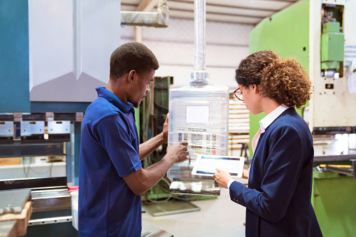 Engineer Controlling Machine In Factory By Manager Stock Photo - Download Image Now