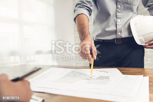 Engineer discussing construction plan blueprint with client in the engineer discussing construction plan blueprint with client in the office stock photo istock malvernweather Image collections