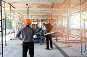 istock Engineer discussing with foreman about project in building construction site 959319496