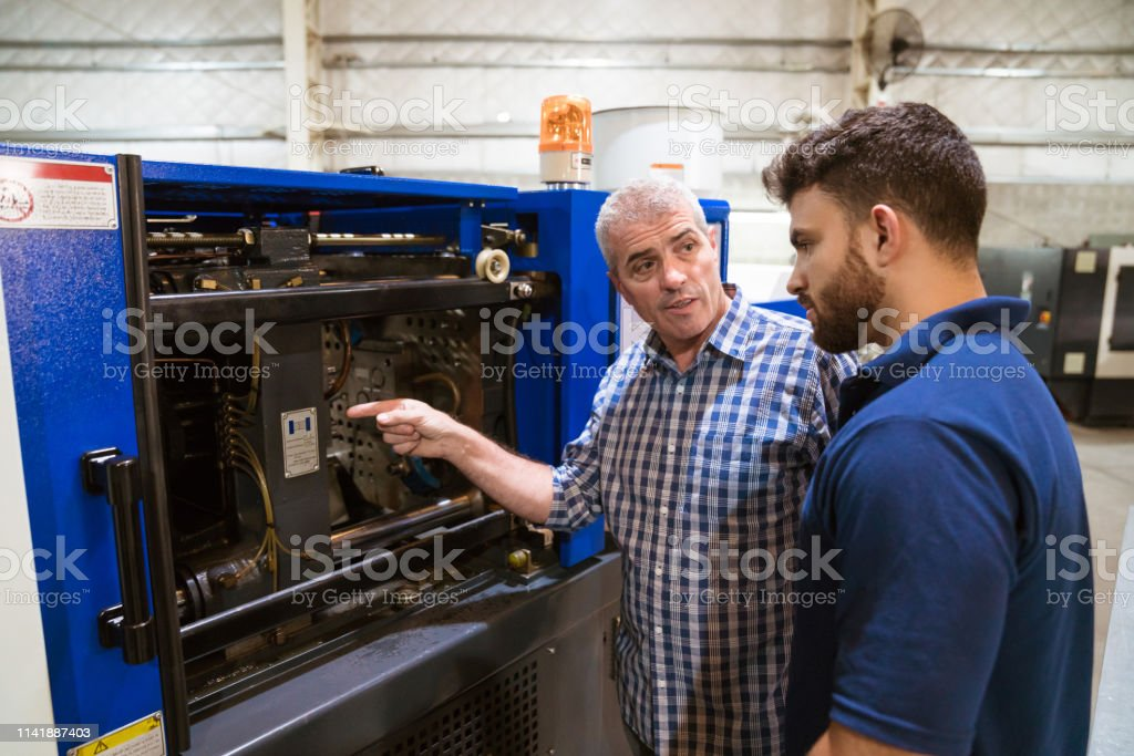 Engineer discussing with trainee over machinery Mature engineer explaining apprentice over injector machine. Instructor is teaching male trainee in industry. They are in factory. 20-24 Years Stock Photo