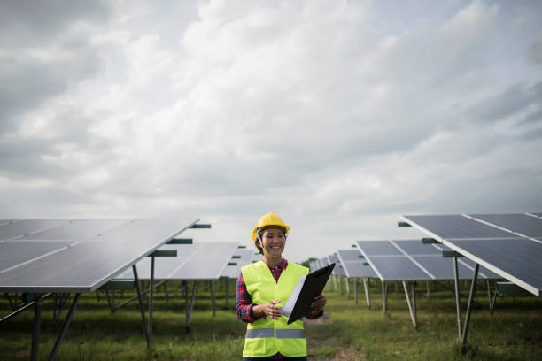 Engineer electric woman checking and maintenance of solar cells. stock photo