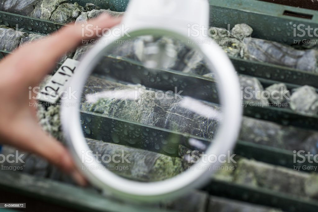 Engineer examining ore specimens with magnifying glass stock photo