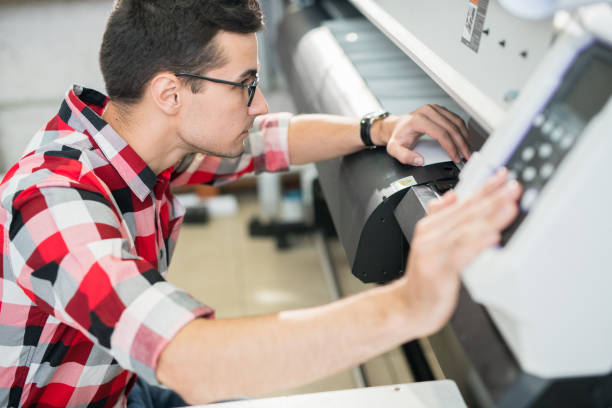 Engineer examining wide format printer Serious thoughtful handsome young engineer in shirt examining wide format printer while holding inspection in printing house printing plant stock pictures, royalty-free photos & images