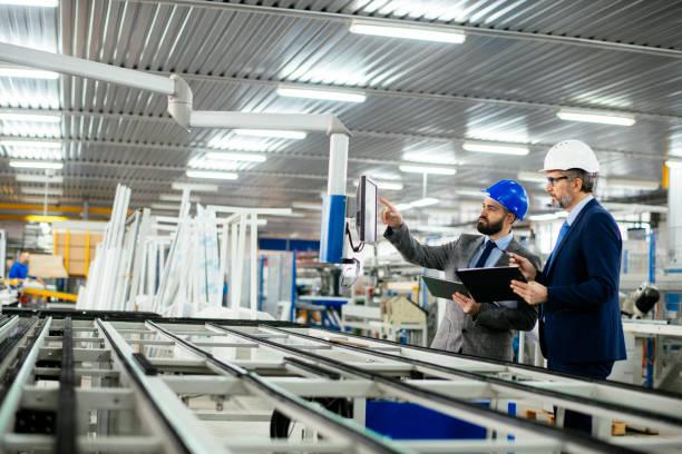 Engineer Explaining Machine Functioning To Company CEO stock photo