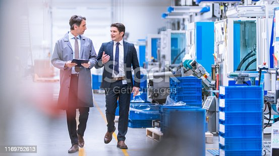 Engineer in a grey coat walking with company CEO through a factory.